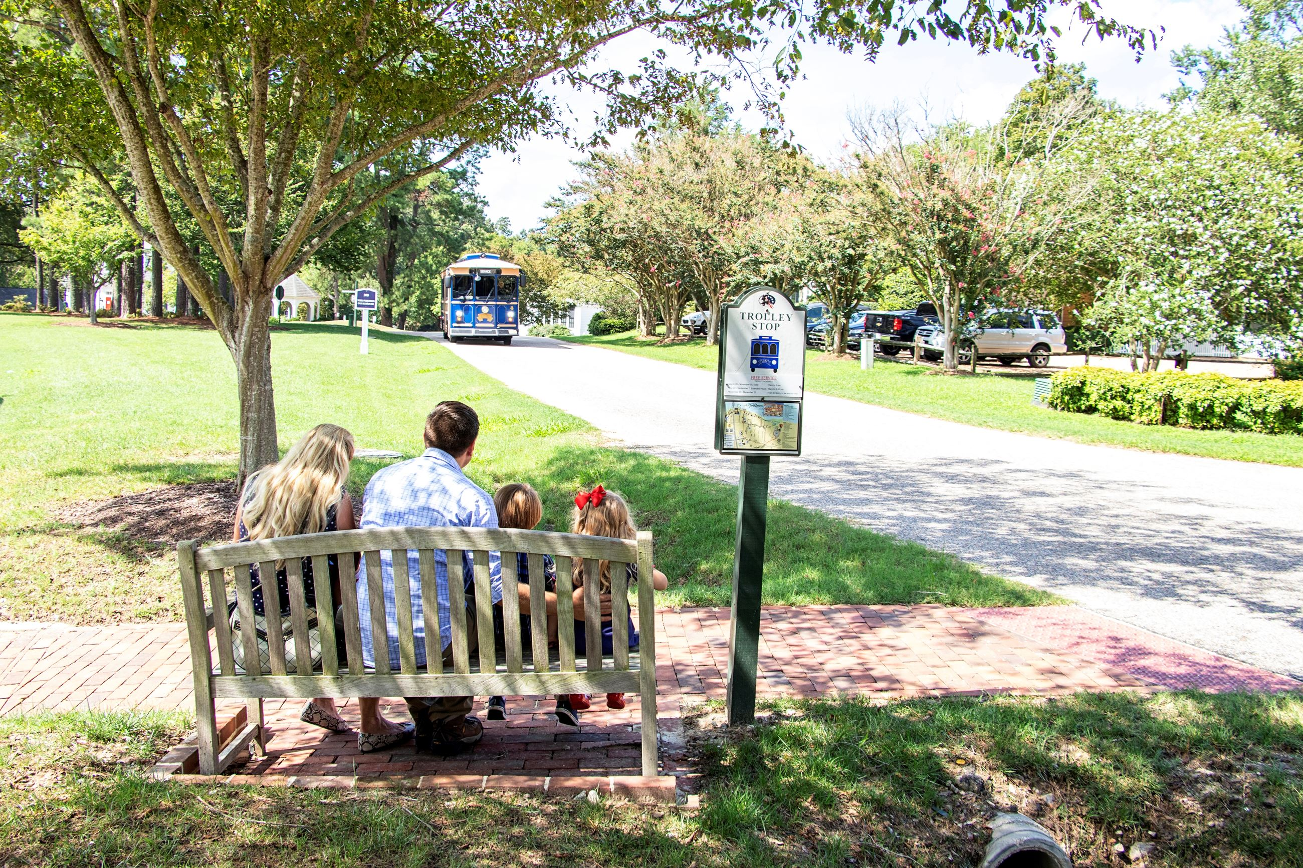 Family waiting at Trolley Stop as it pulls up