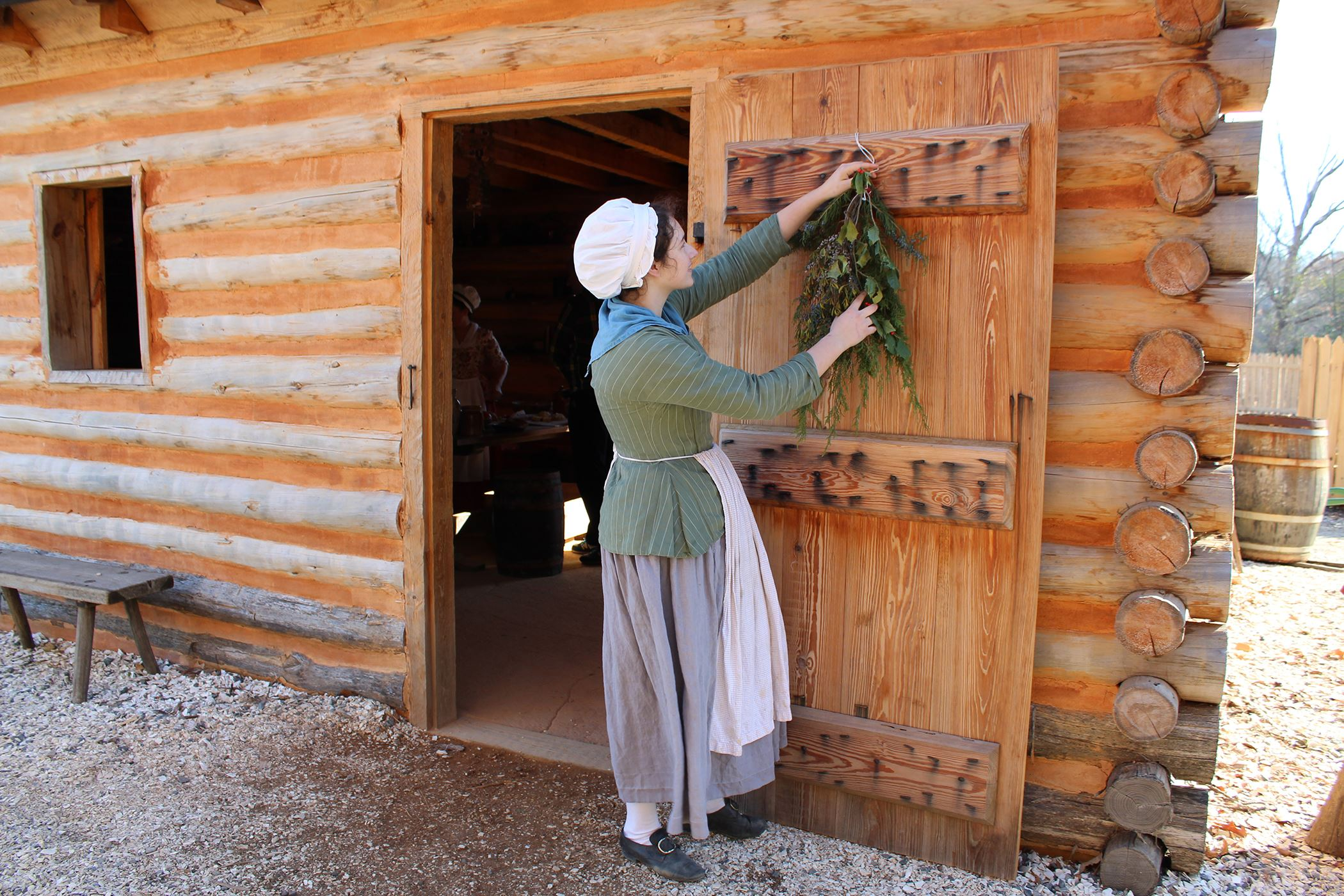 Colonial Interpreter Hanging Christmas Greenery at Outdoor Encampment at American Revolution Museum