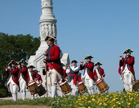 Men in traditional revolutionary clothing play the fife and drums during an event.