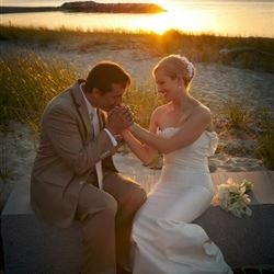 Groom Kisses Brides Hand on Beach